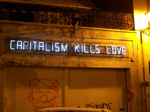 Neon sign that reads capitalism kills love on the street.